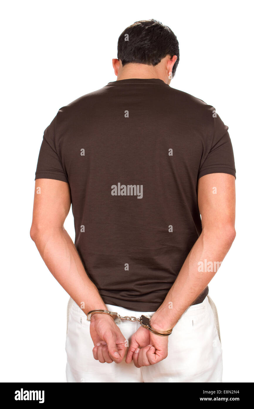 Arrested criminal stands with his hands handcuffed behind his back. - Stock Image