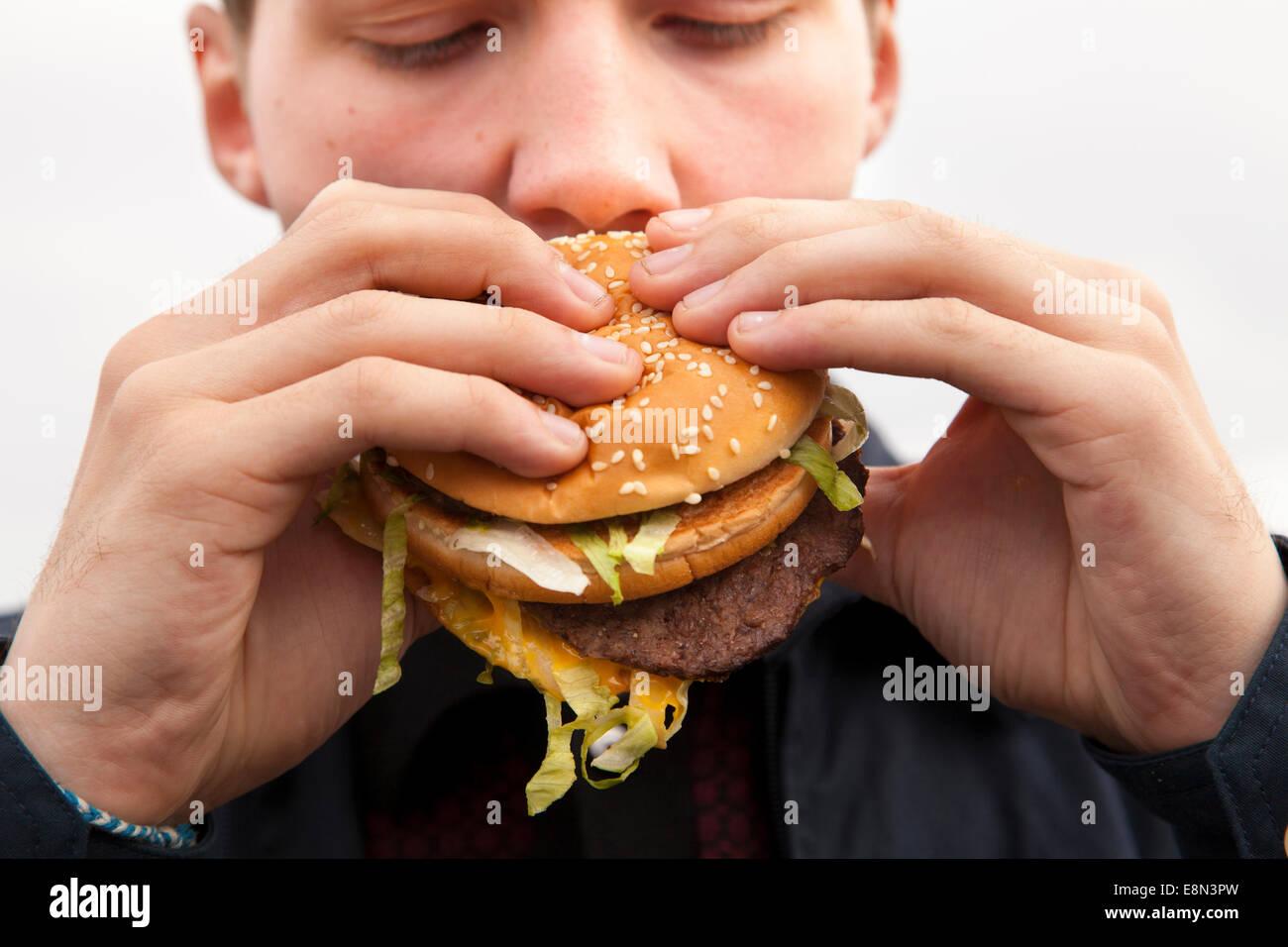 A teenager eating a McDonald's Big Mac burger. - Stock Image