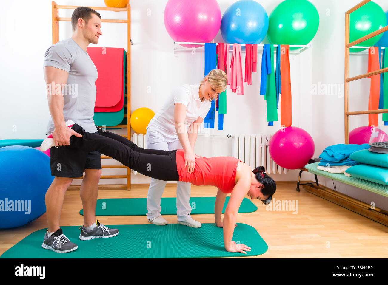 Patients at the physiotherapy doing physical exercises with therapist - Stock Image