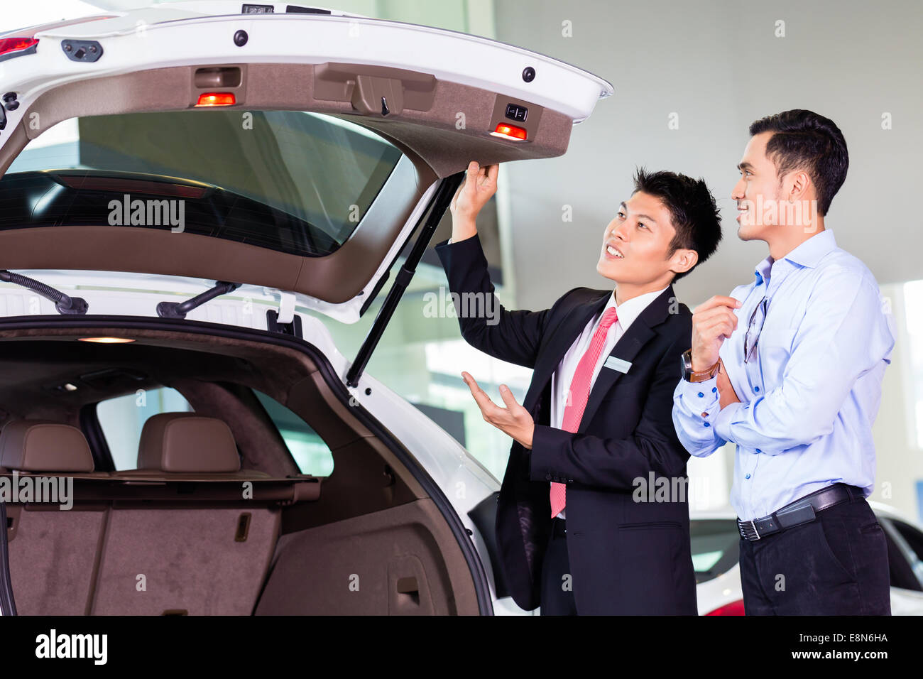 Car salesman in Asian dealership showing trunk of SUV car to customer - Stock Image
