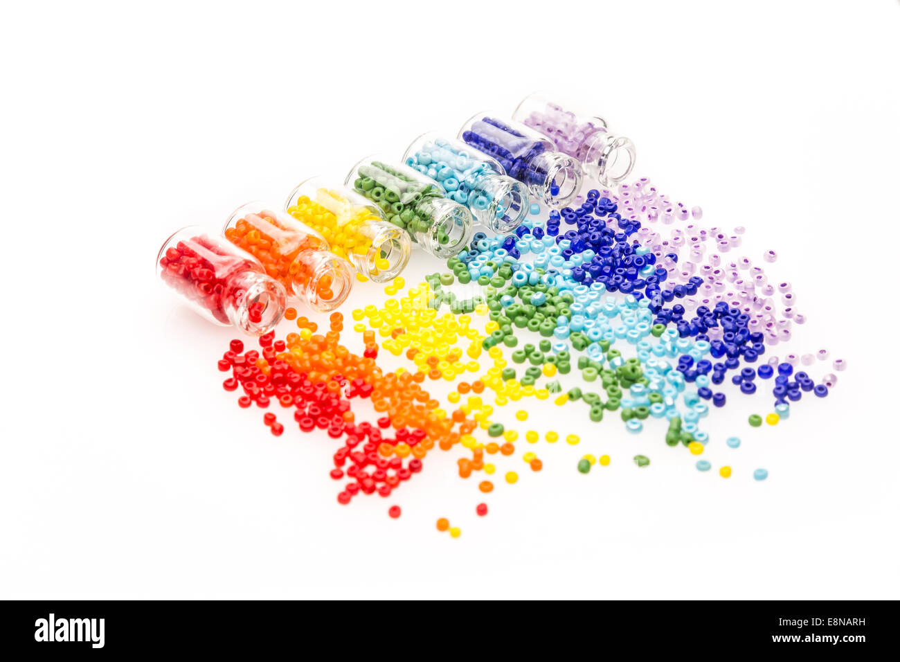 Tiny glass bottles filled with a rainbow colors of beads spilling out, on a white background Stock Photo