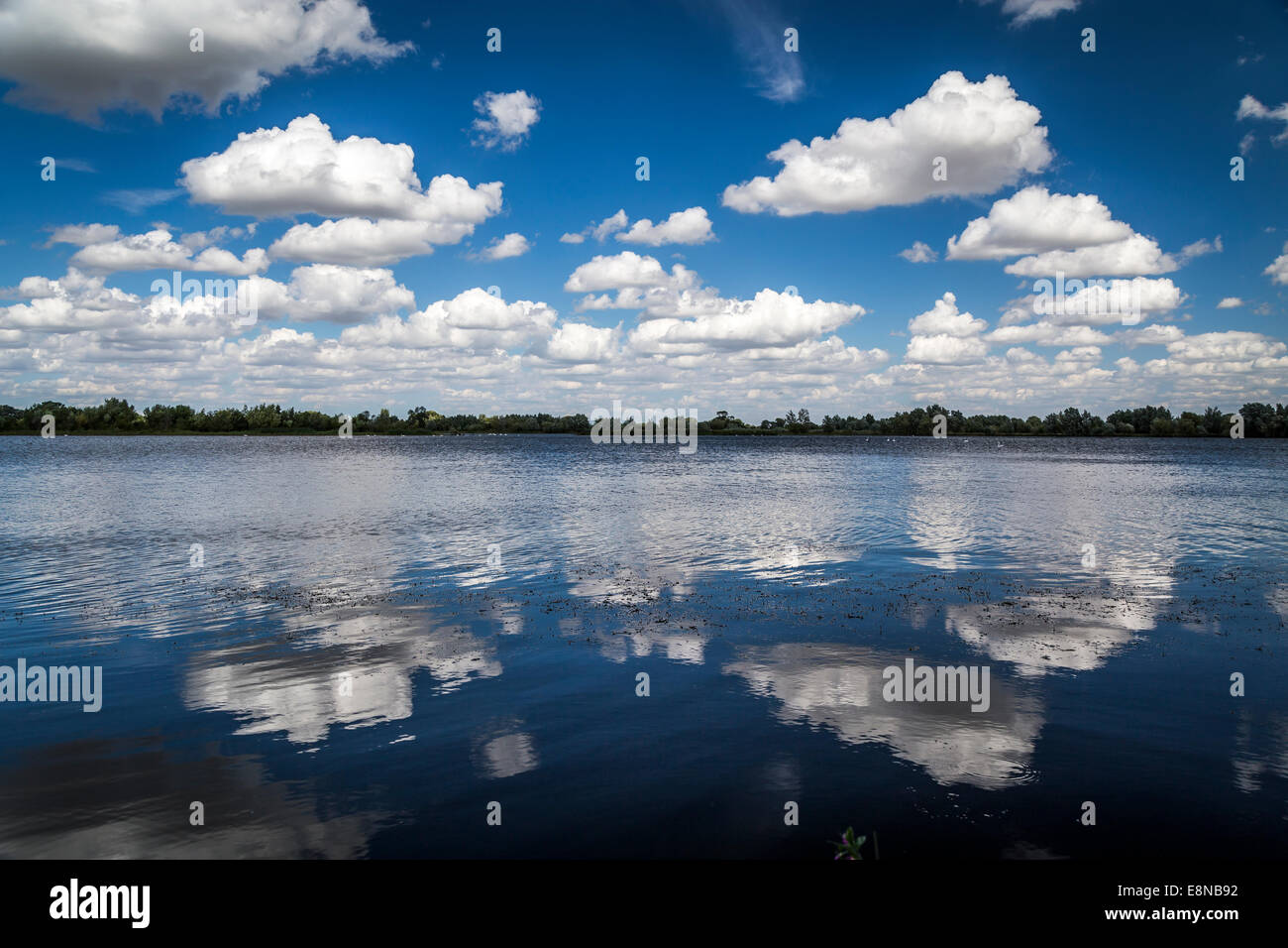 Reflections of white fluffy clouds in a lake on a blue, sky, sunny day - Stock Image