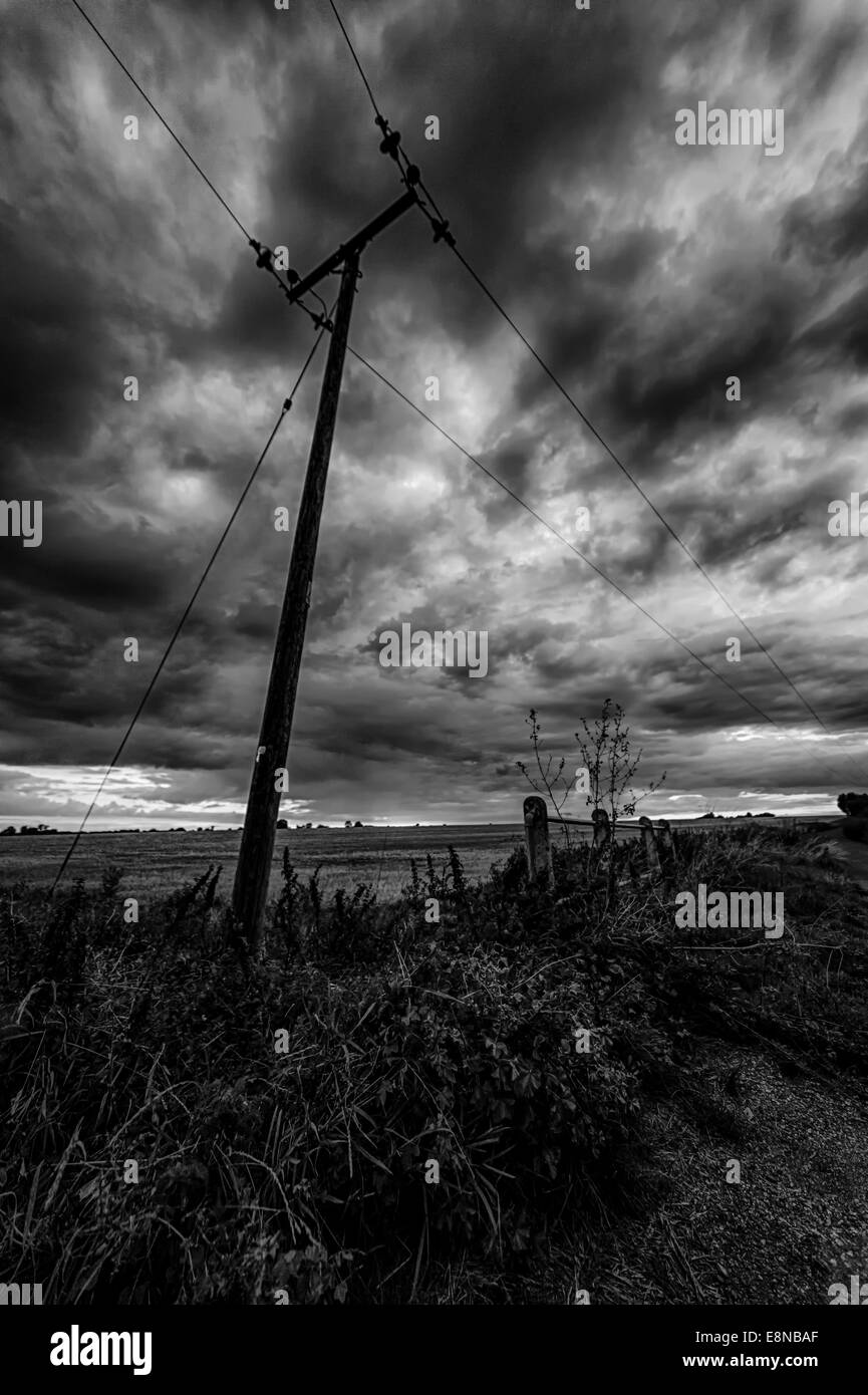 Silhouette of a telegraph pole at dusk with angry dark clouds in the sky in black and white - Stock Image