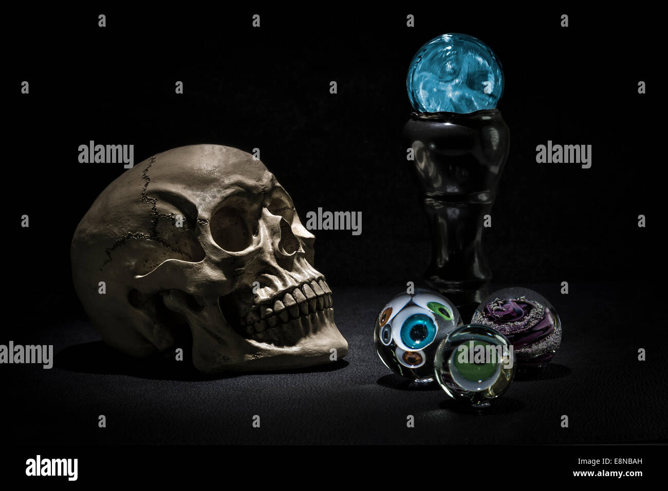Dark and shadowy human skull in a pool of light. Crystal balls with eyeballs looking out - Stock Image