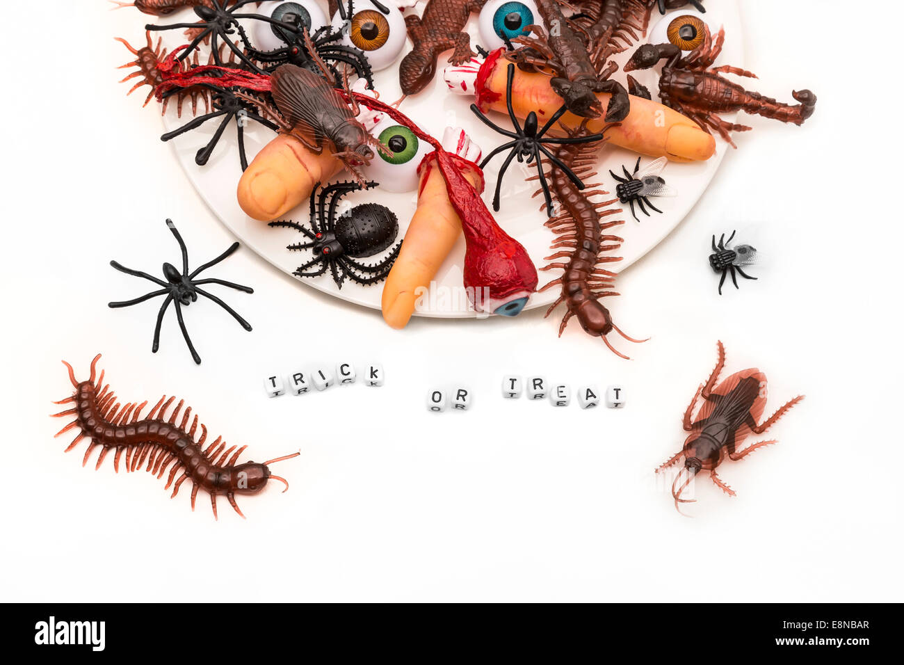 Trick or treat words surrounded by candy bugs, joke plastic fingers and eyeballs on an overflowing dish onto a white - Stock Image