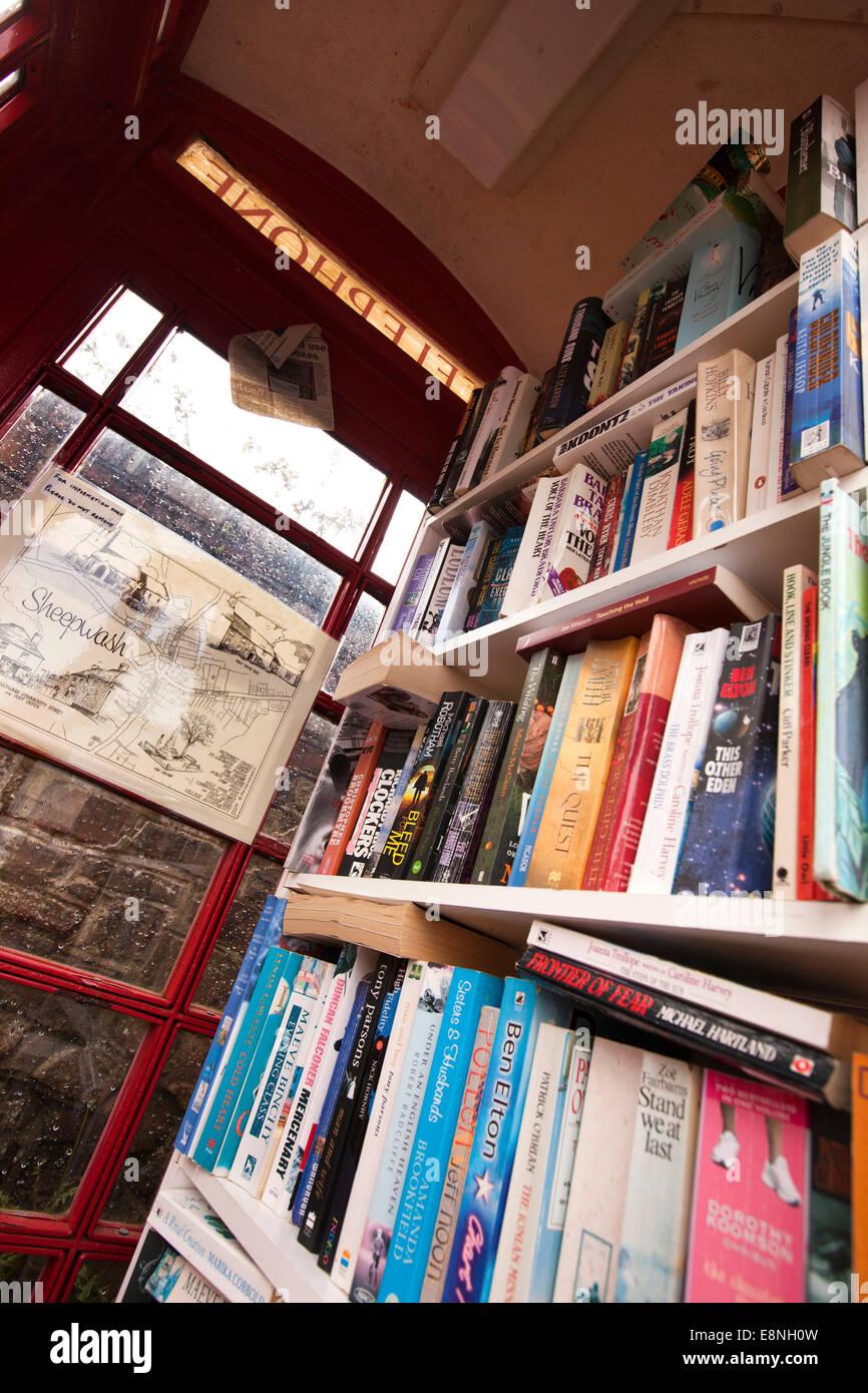 UK, England, Devon, Sheepwash, redundant old red K6 phone box used as village book exchange - Stock Image