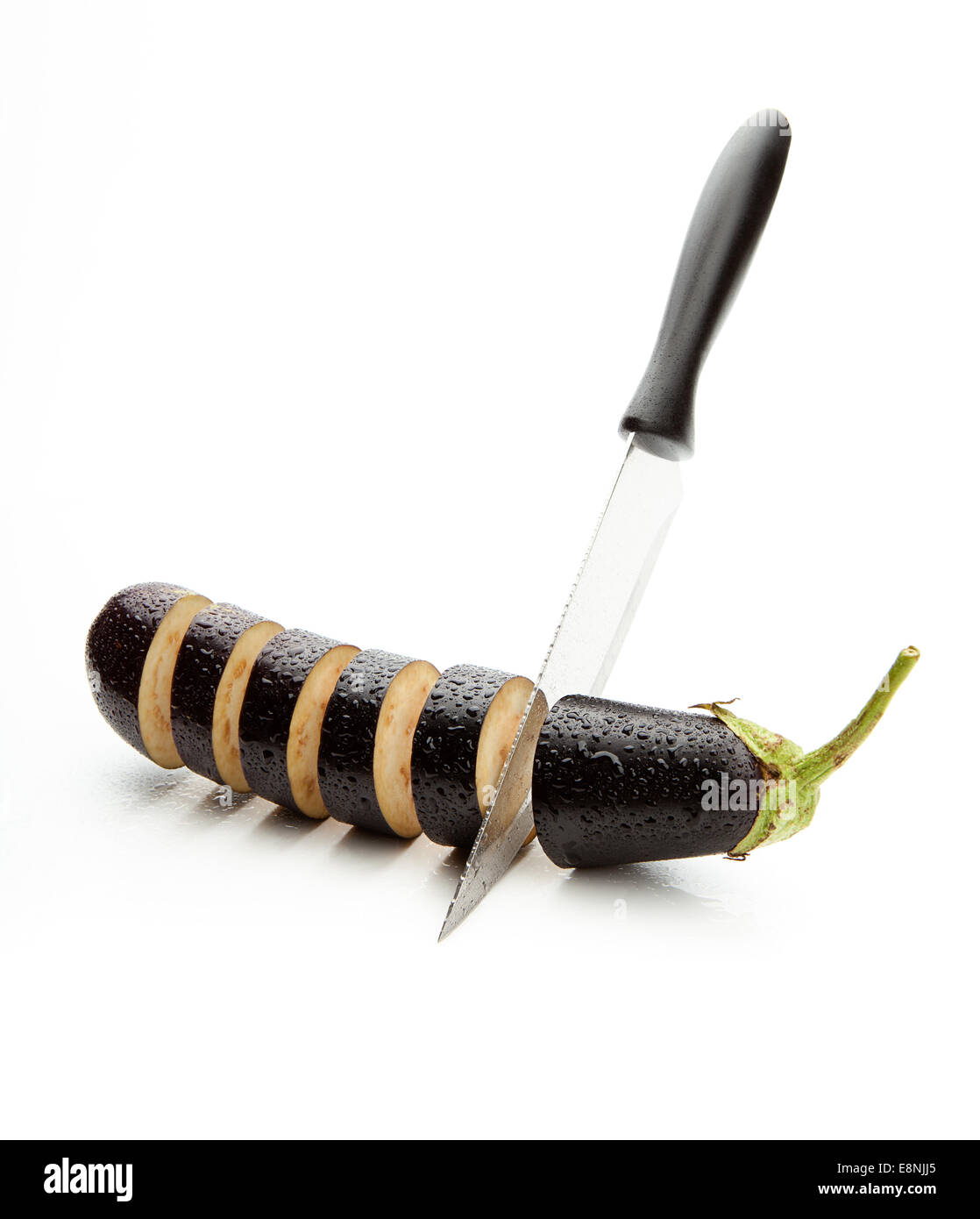 sharp knife, cut the wet eggplant into pieces on white background - Stock Image