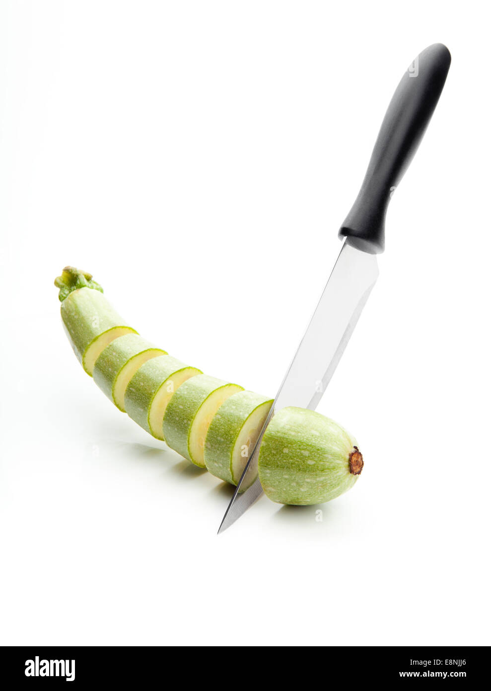 sharp knife, cut into pieces of squash on a white background - Stock Image
