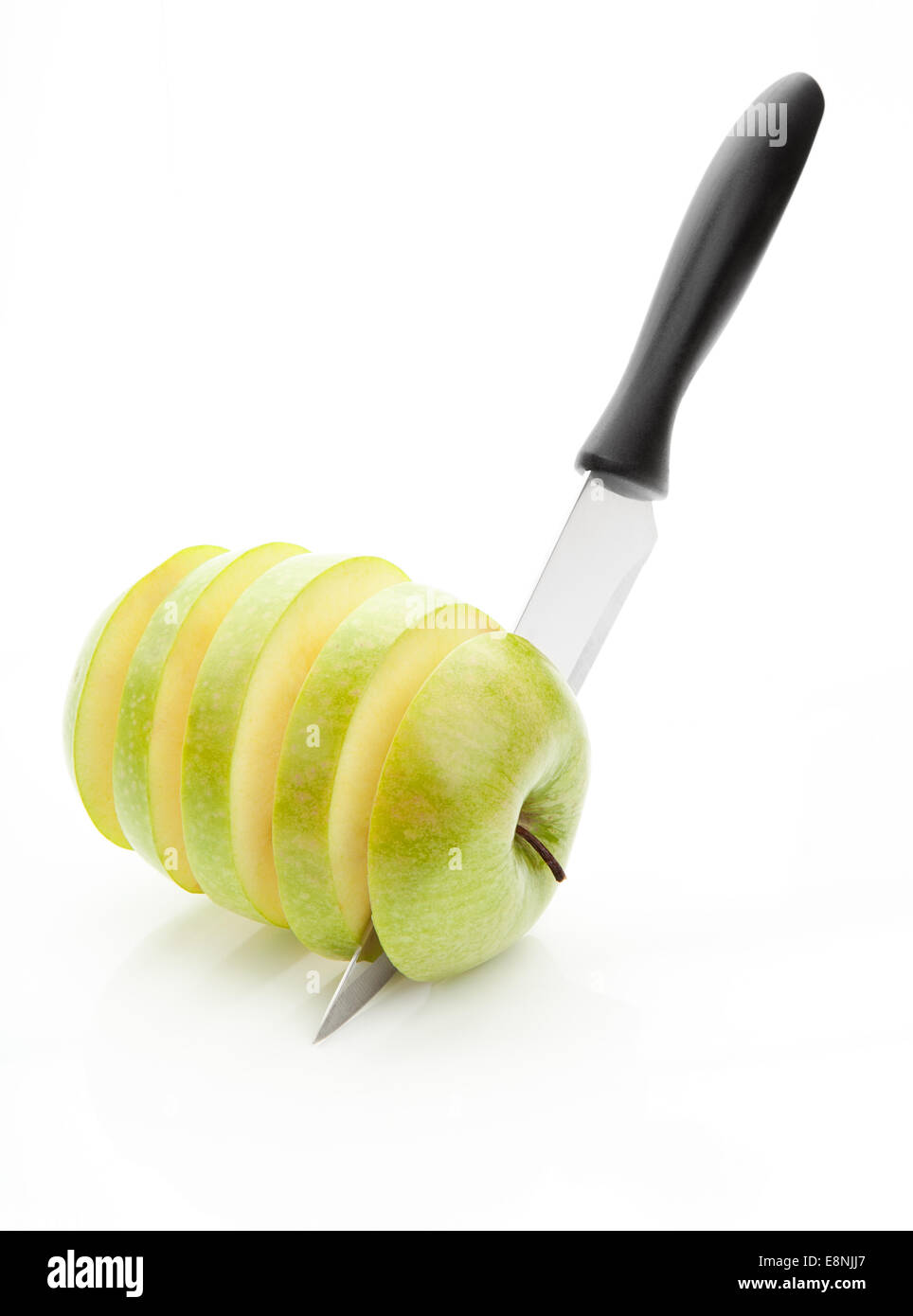 sharp knife, cut into pieces green apple on a white background - Stock Image