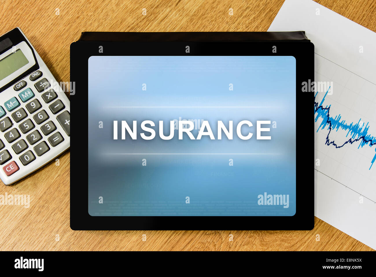 insurance word on digital tablet with calculator and financial graph - Stock Image