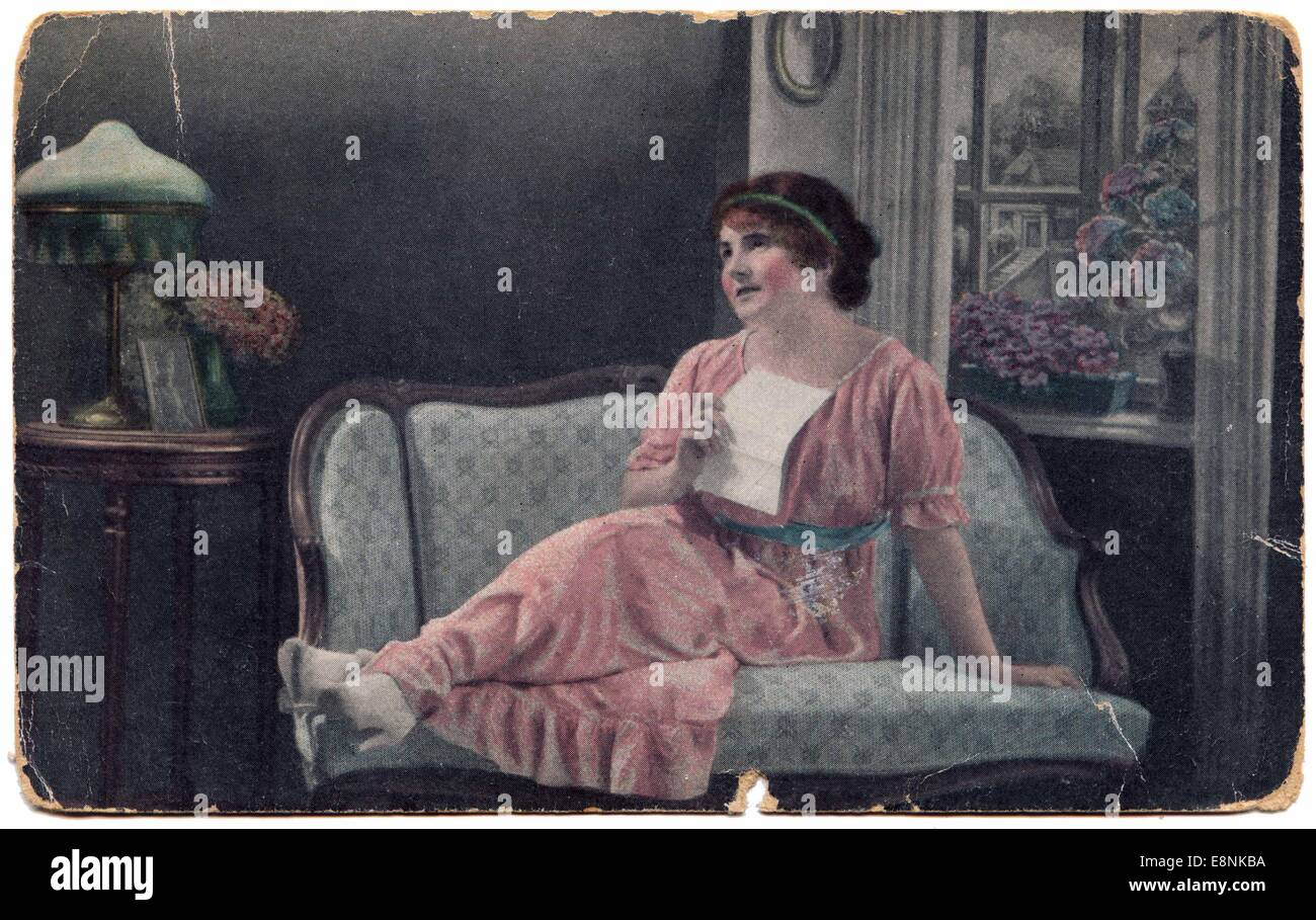Woman sitting on the couch, dreamily presses to her bosom a love letter. 29th Sep, 2010. Antique postcards, Russia, - Stock Image