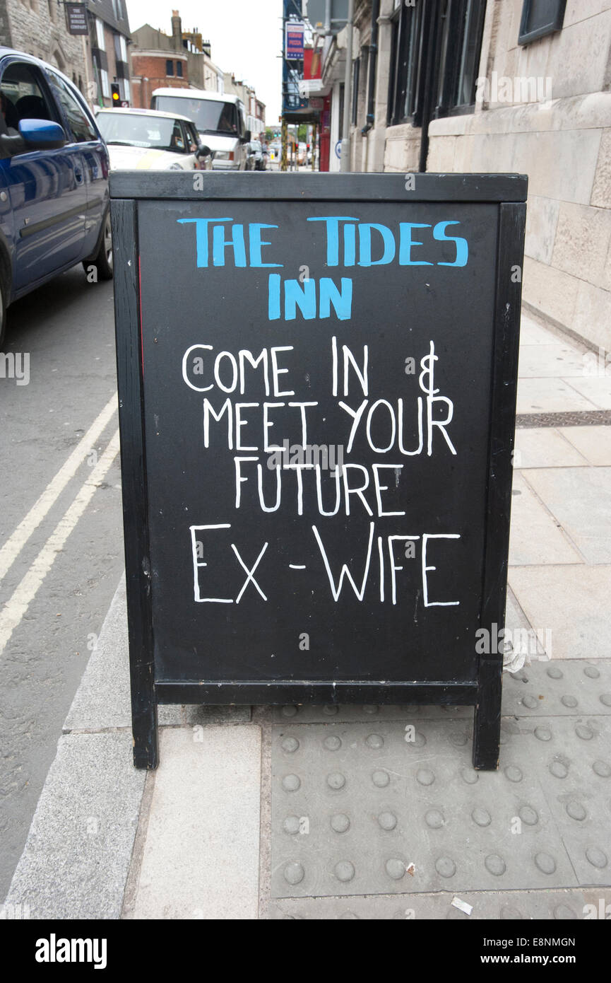 A quirky pub sign written on an 'A' board outside 'The Tides Inn' public house in Weymouth - Stock Image