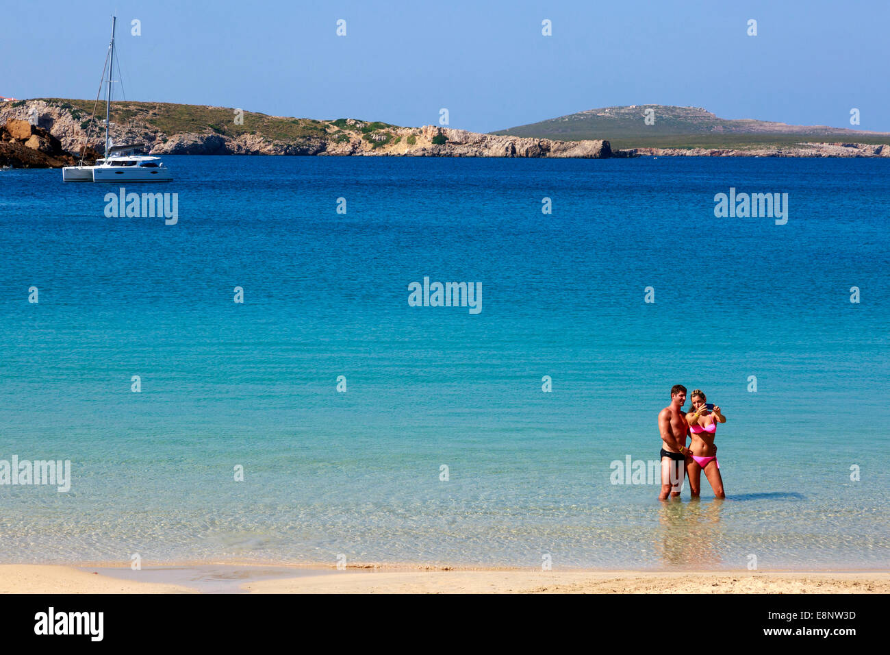 Man and woman on holiday taking a 'selfie' photograph while standing in the sea at Arenal d'en Castell, - Stock Image
