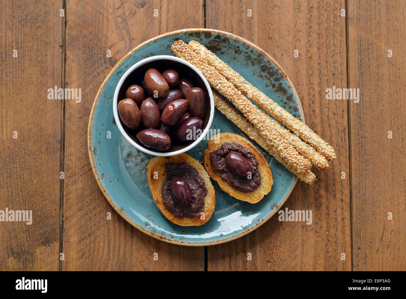 Bread with olive pate on plate closeup. Greek cuisine - Stock Image