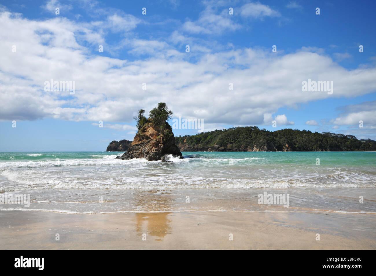 Flat sandy beach with coastal rocks at low tide in Matapouri, Tutukaka Coast in New Zealand. - Stock Image