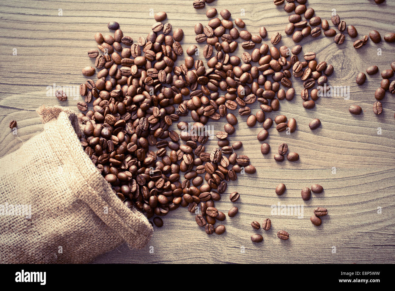 the coffee beans spill out of the sack - Stock Image
