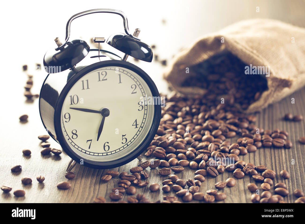 vintage alarm clock and coffee beans on wooden table - Stock Image