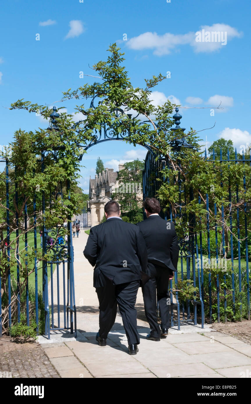 Members of Trinity College pass through the gate from the Garden Quadrangle to the College Gardens. - Stock Image