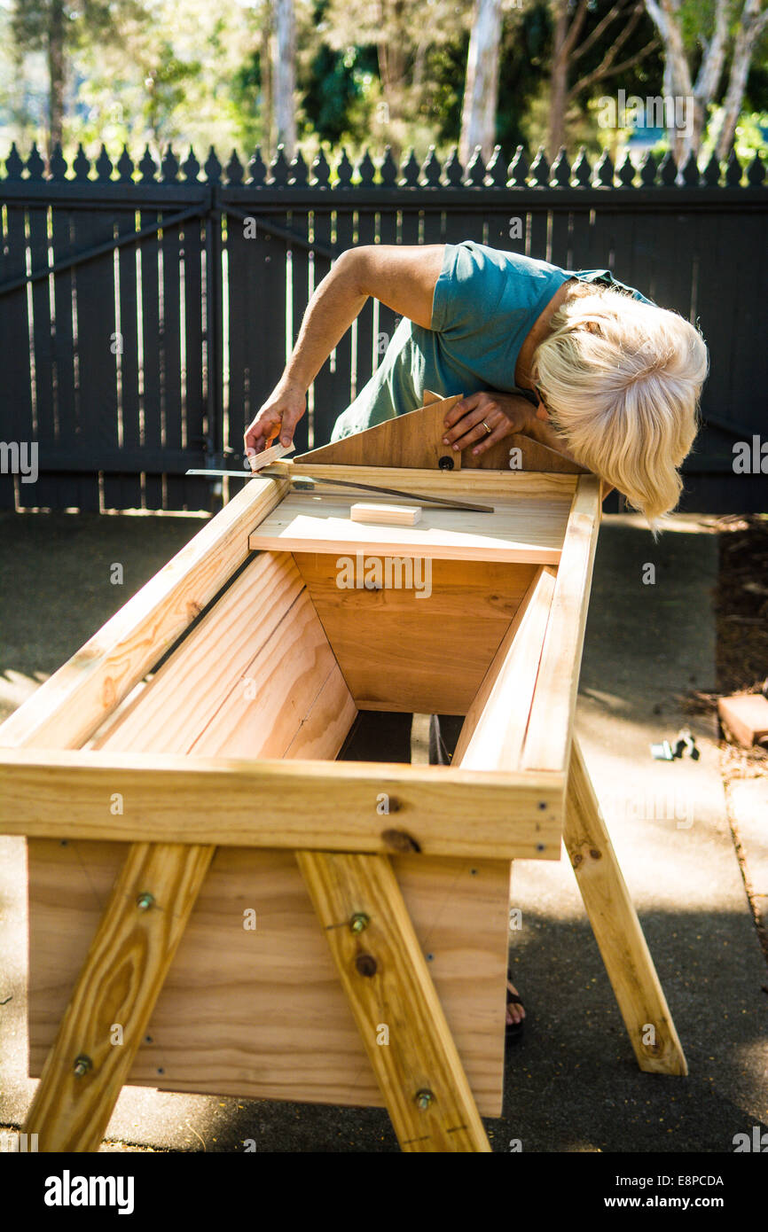 Woman making a top bar beehive, Brisbane, Queensland, Australia - Stock Image