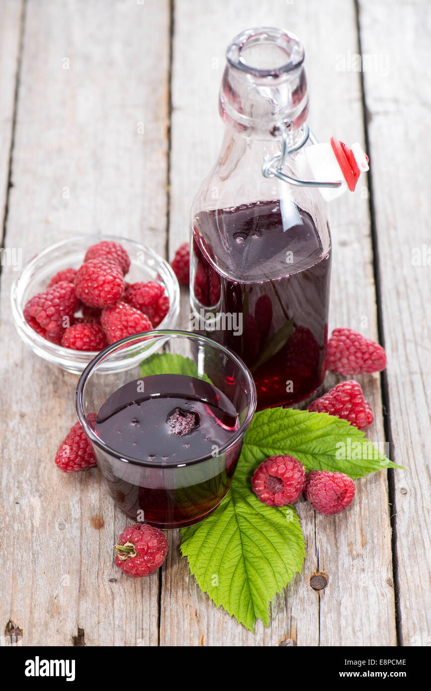 Raspberry Sirup in a glass (with fresh fruits) - Stock Image