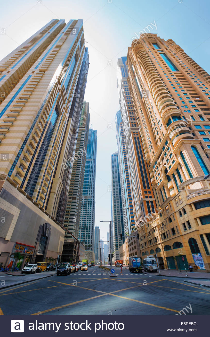 Street lined with new apartment skyscrapers in Dubai United Arab Emirates - Stock Image