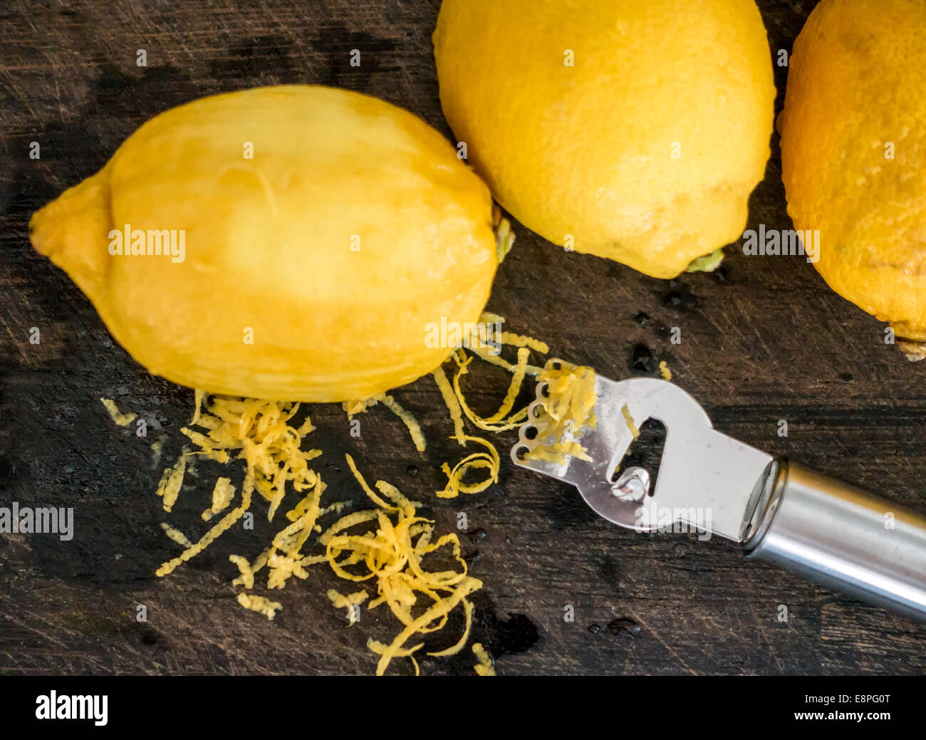 Peeling lemon rind to add zest to cook - Stock Image