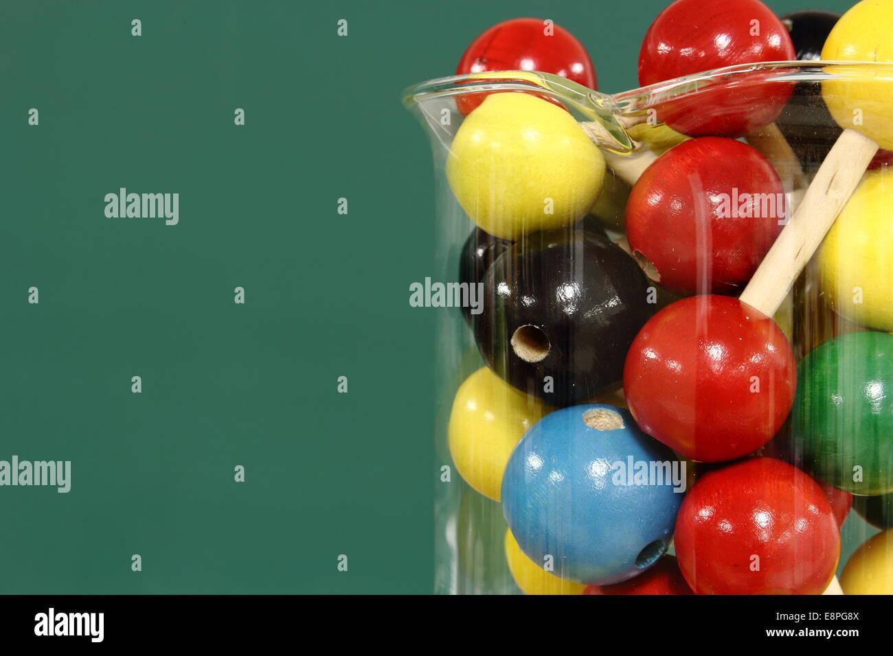 Molecular model: wooden balls in a beaker on a background of green blackboard - Stock Image