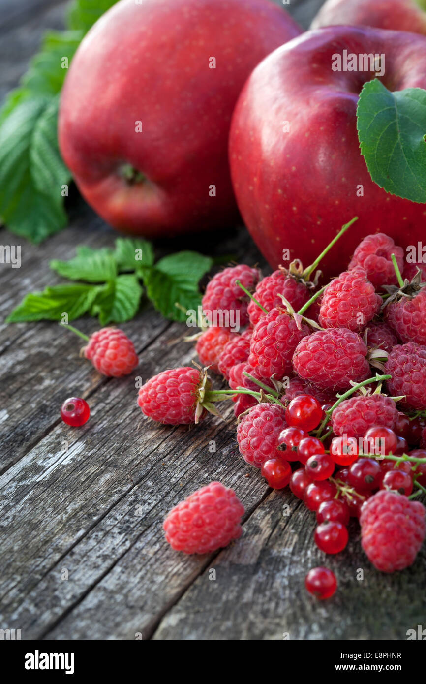 Redcurrant, rasberry and red apples on old wooden table, mix of red color vitamins concept Stock Photo
