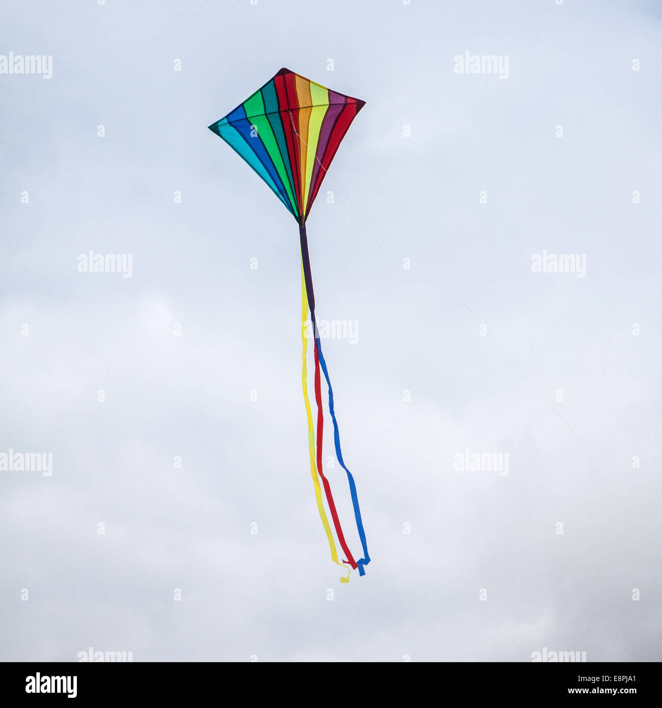 Rainbow coloured kite flying against a cloudy sky, West Sussex, England, United Kingdom. - Stock Image