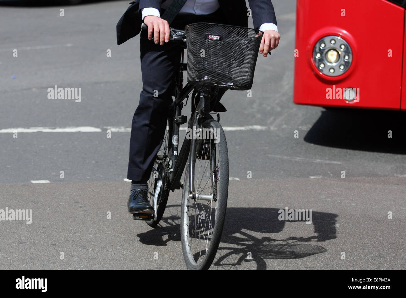 A city gent cycling in front of a red London bus - Stock Image