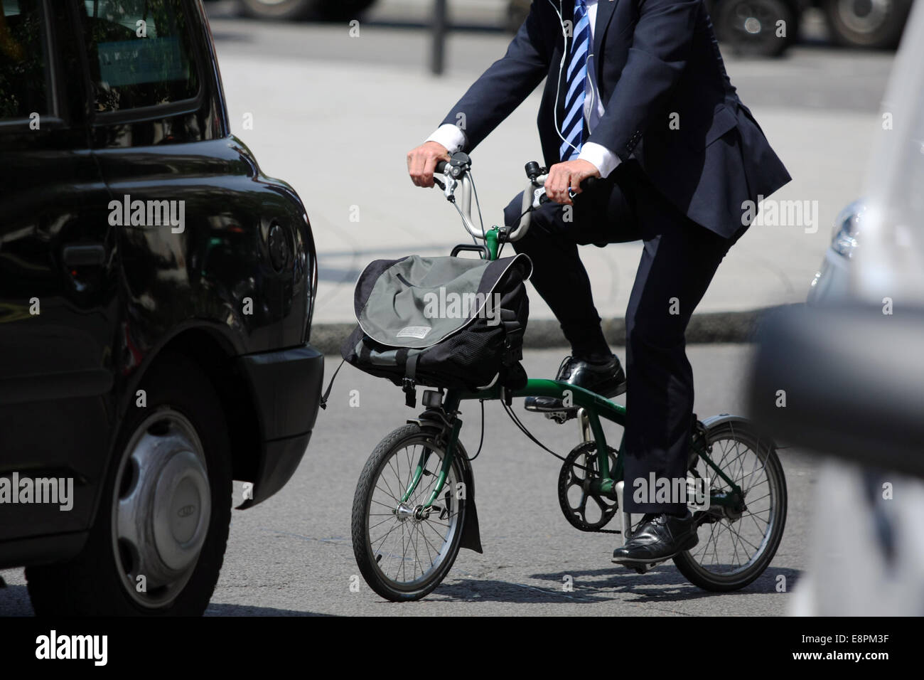 A city gent rides a folding cycle in London traffic - Stock Image