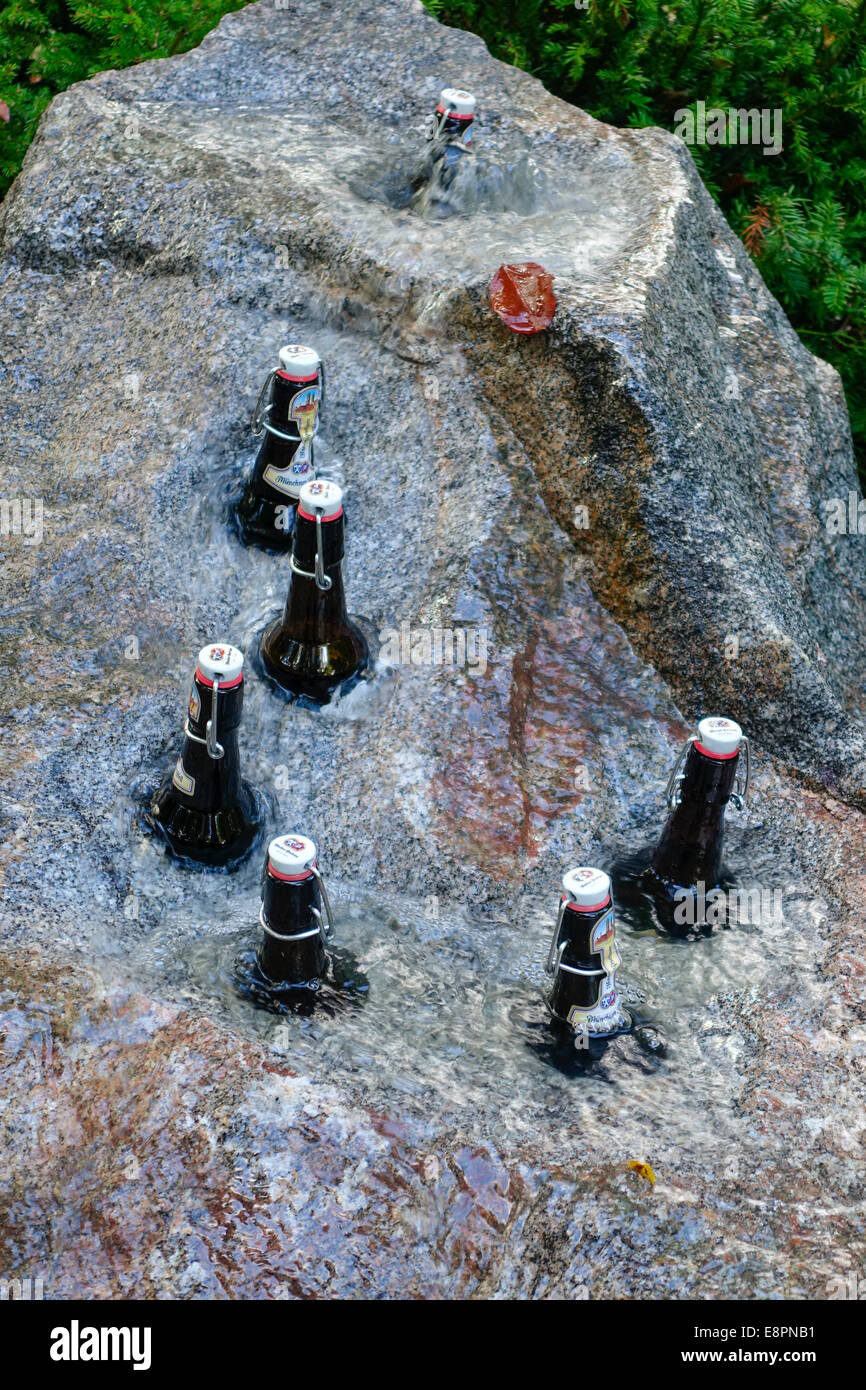 Beer bottles are cooled in a stone fountain - Stock Image