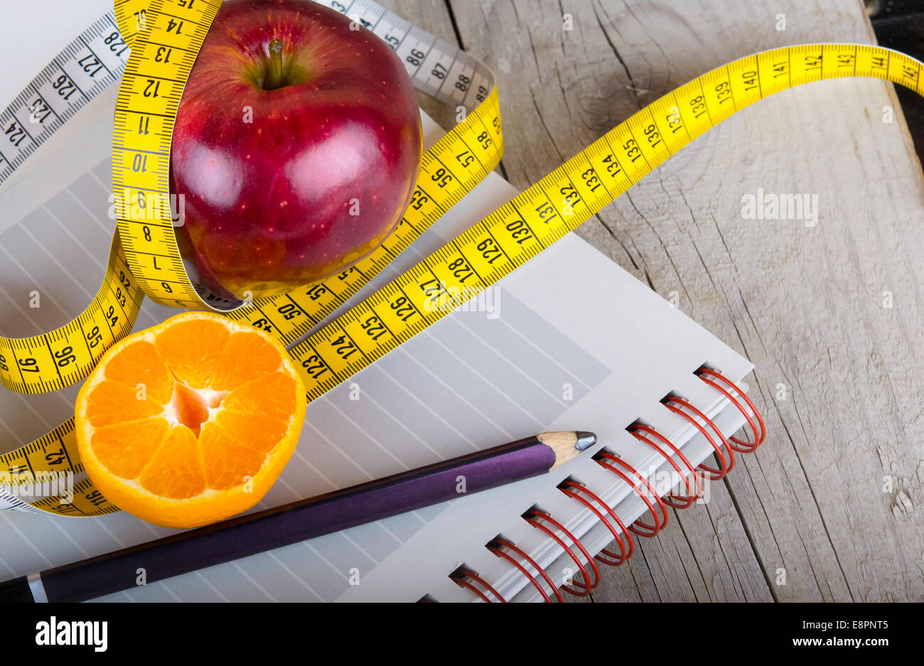 Measuring tape wrapped around a apple weight loss - Stock Image