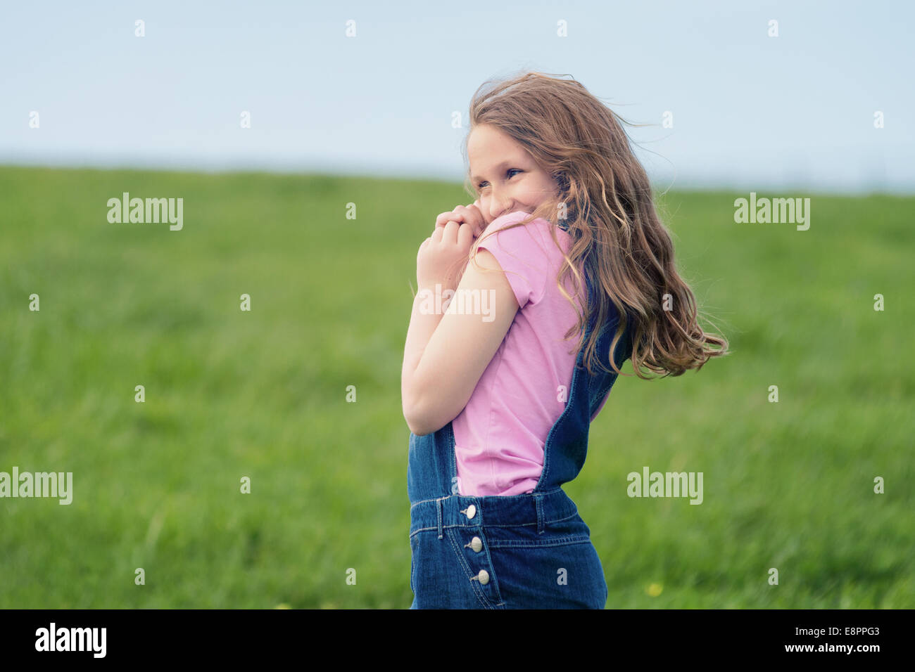 happy laughing girl in a field, wearing denim and pink - Stock Image