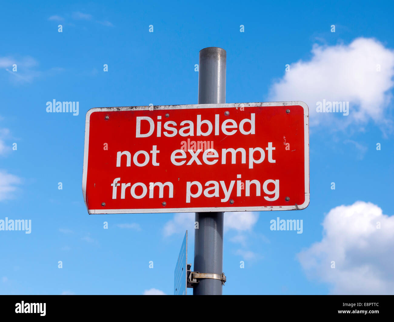 Sign reading Disabled Not Exempt From Paying in a train railway station car park - Stock Image