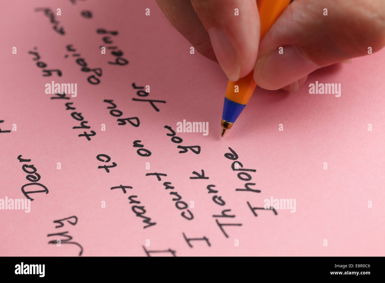 Writing letter to a friend on pink paper. - Stock Image