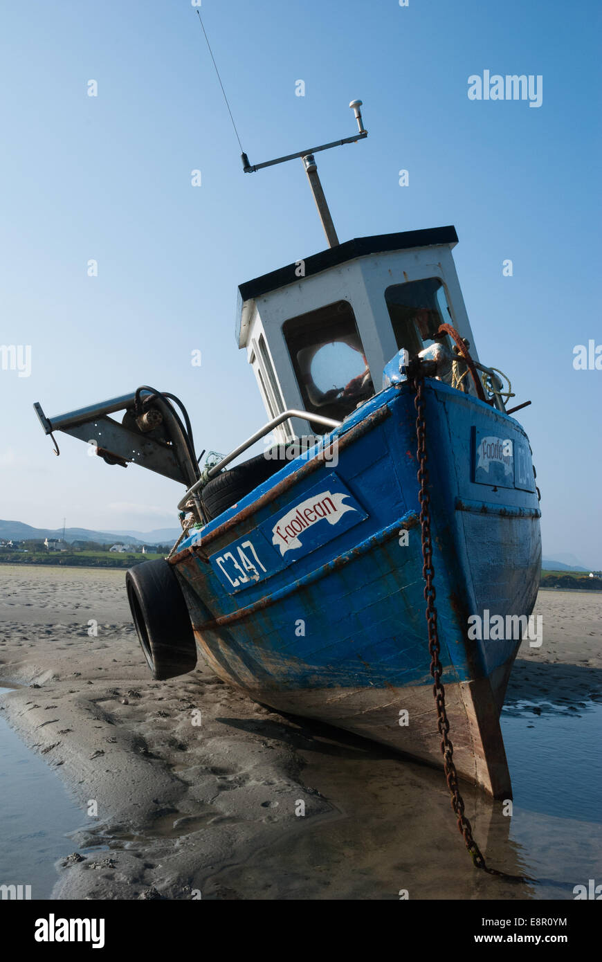 A local fishing boat stranded at low tide in Dunfanaghy Bay, County Donegal, Ireland. - Stock Image