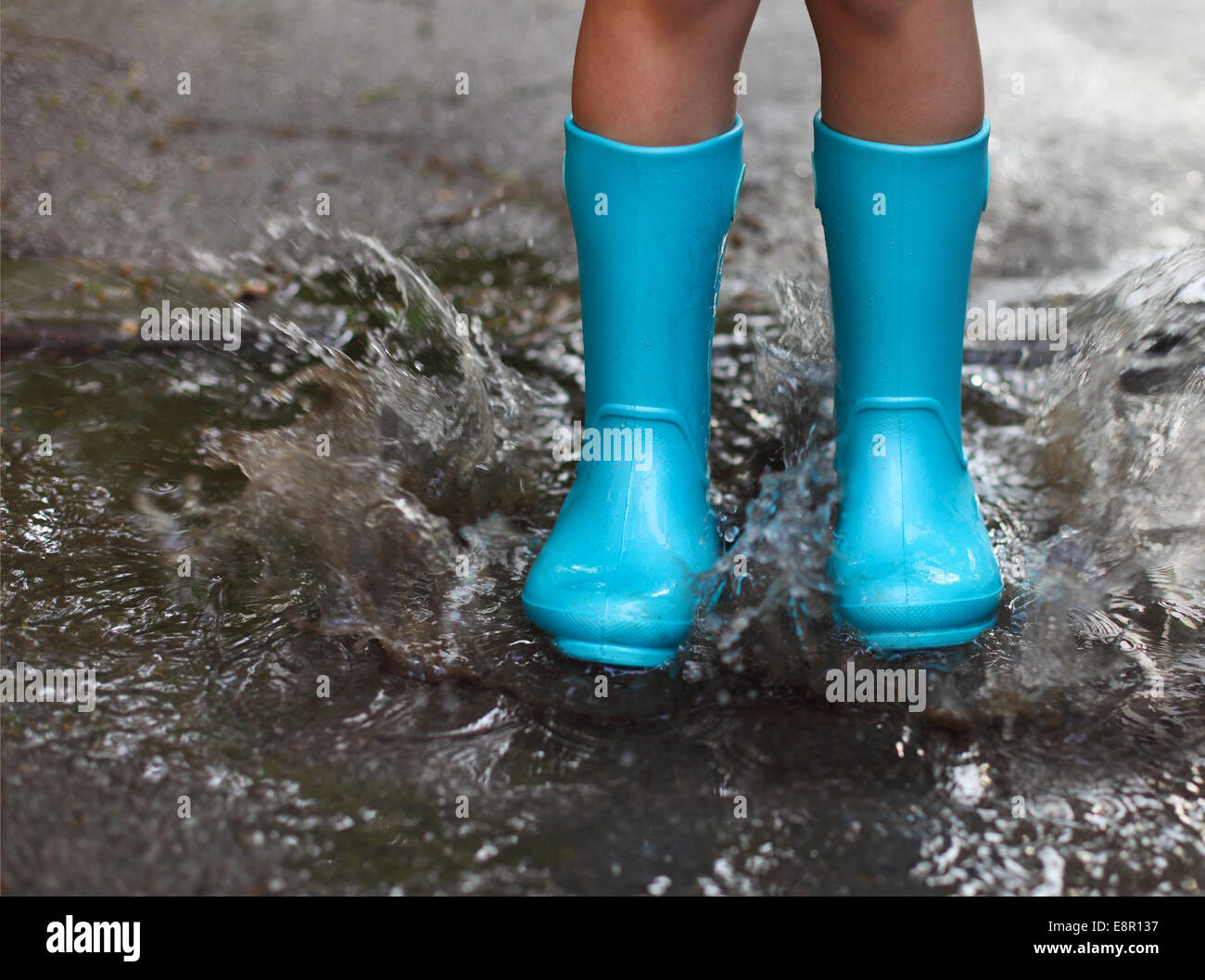 86d495eb6a0 Child wearing blue rain boots jumping into a puddle. Close up Stock ...