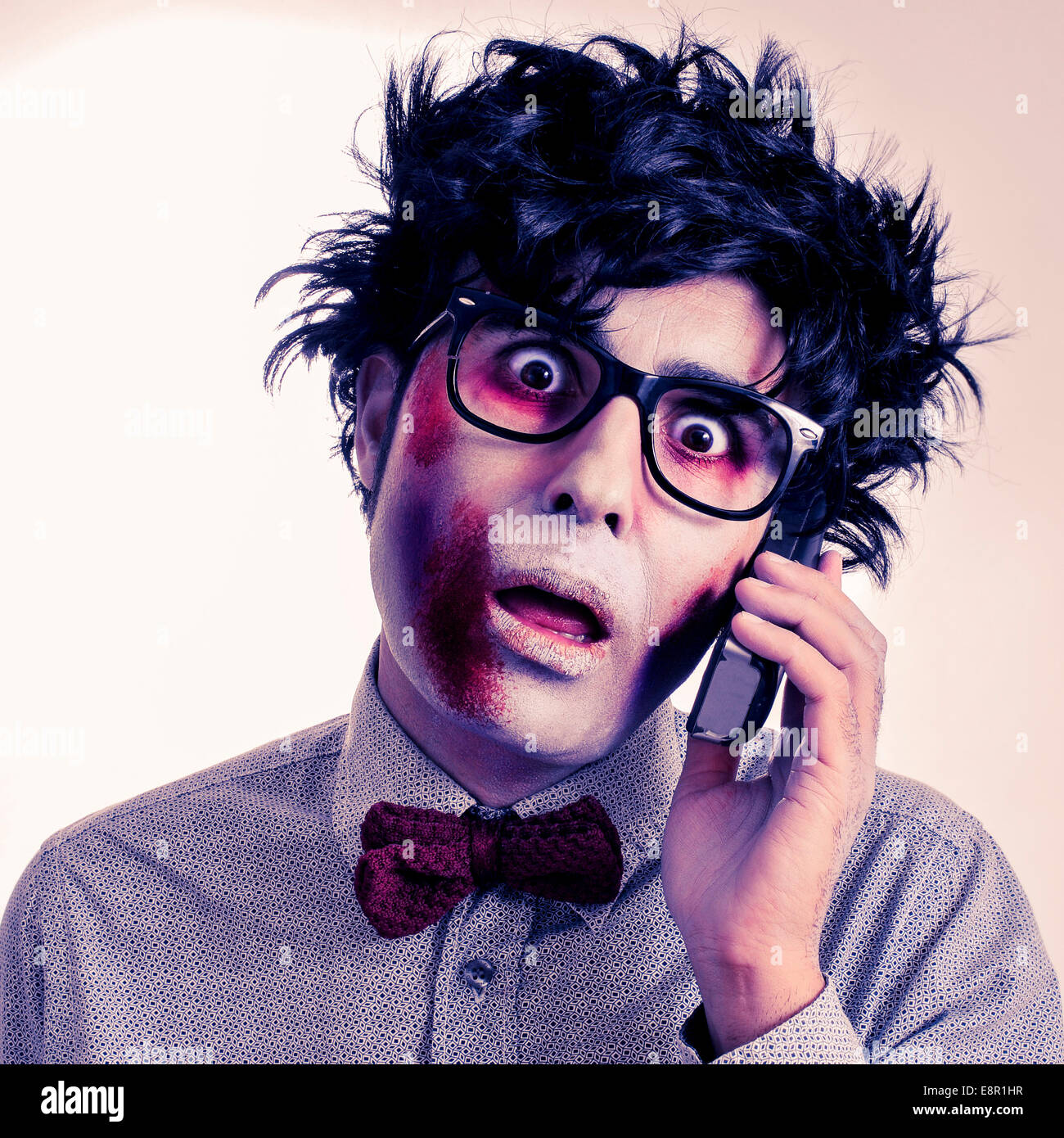 a scary hipster zombie with black plastic-rimmed eyeglasses talking on the phone, with a retro effect - Stock Image