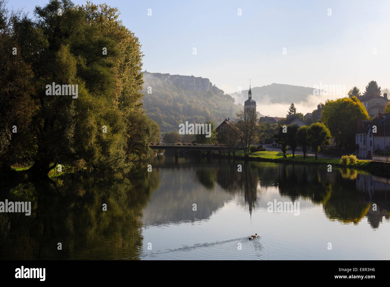 Tranquil scene on River Loue with early morning autumn mist in Loue valley in Jura mountains. Ornans Doubs Franche - Stock Image