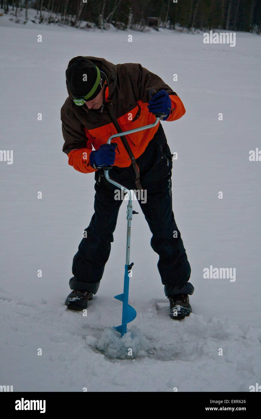 Lapp guide demonstrating traditional ice fishing technique on Lake Pyhajarvi, Kairos, Finland. - Stock Image