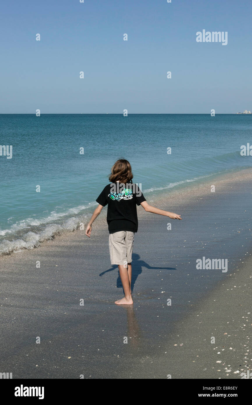 Long haired boy skipping stones, Turtle Beach, Sarasota County, Florida - Stock Image