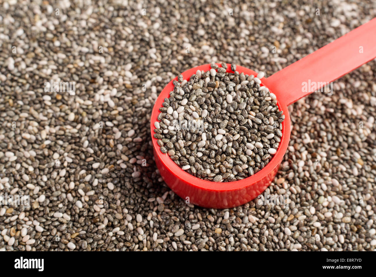 Chia seeds in a red measuring spoon - Stock Image