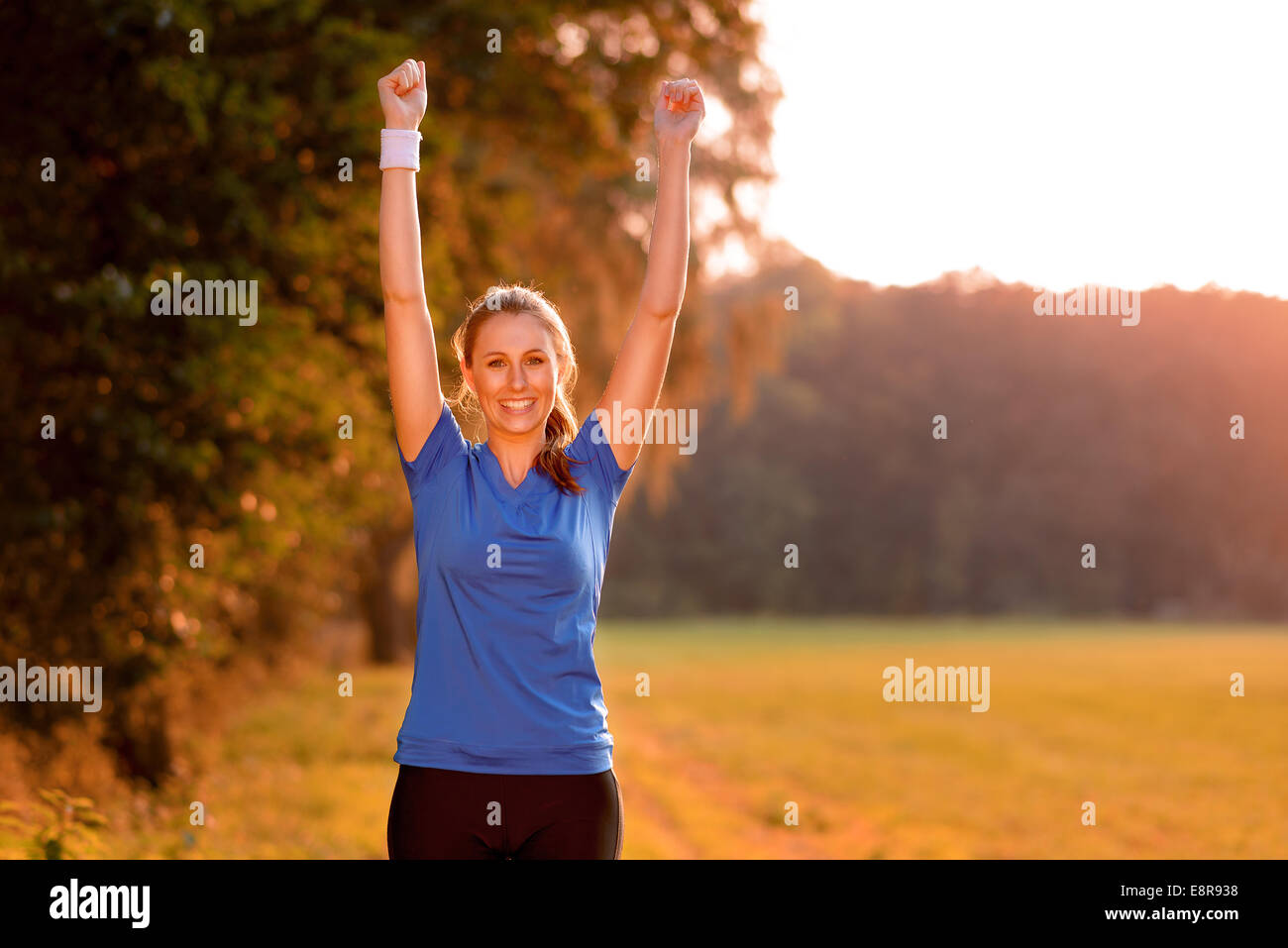 Jubilant young woman punching the air with her raised fists as she celebrates a success while standing in lush green - Stock Image