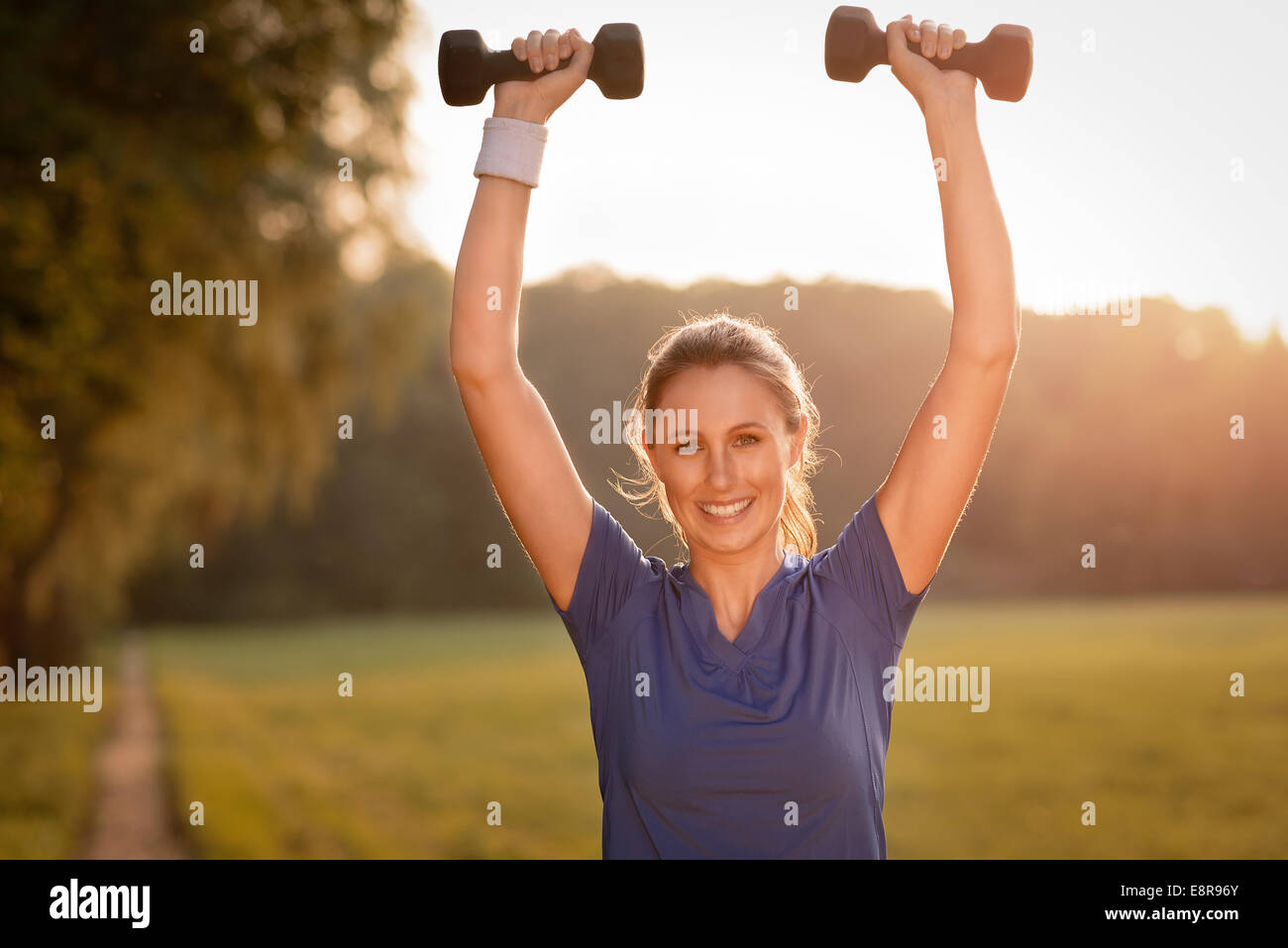 Beautiful young woman working out with dumbbells outdoors in the countryside in evening light looking at the camera - Stock Image