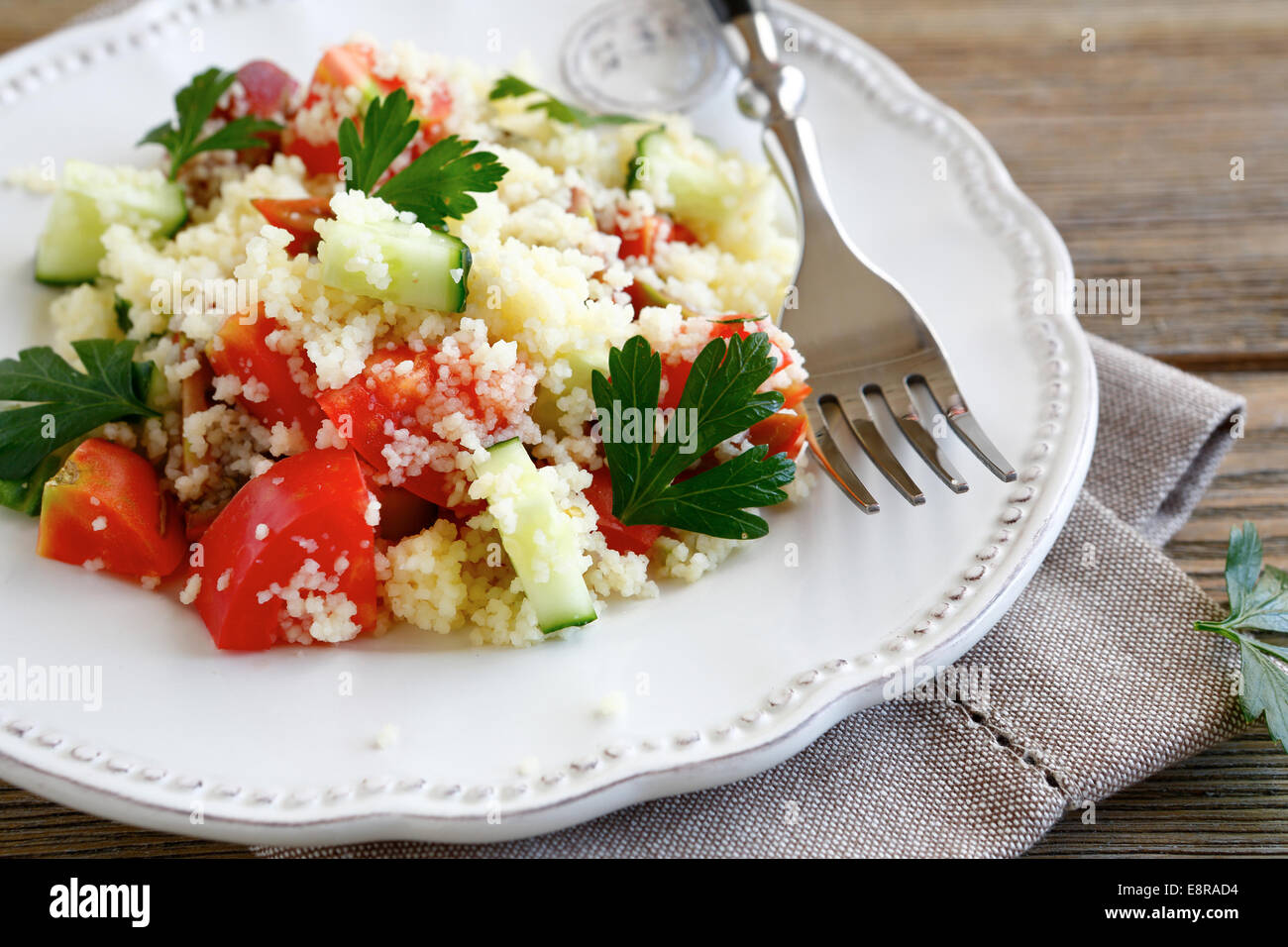 Salad with couscous and vegetables on a white plate, food closeup - Stock Image