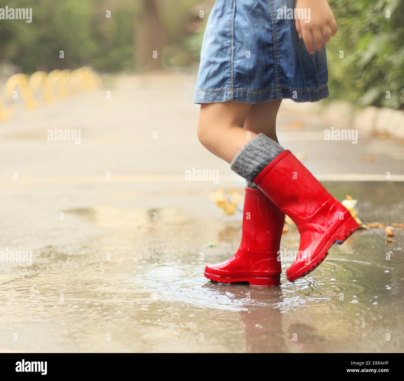 85179086fb1 Child wearing red rain boots jumping into a puddle. Close up Stock ...