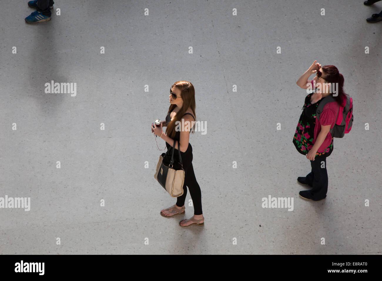 Women passengers waiting for platform information at Brighton Train Station. - Stock Image