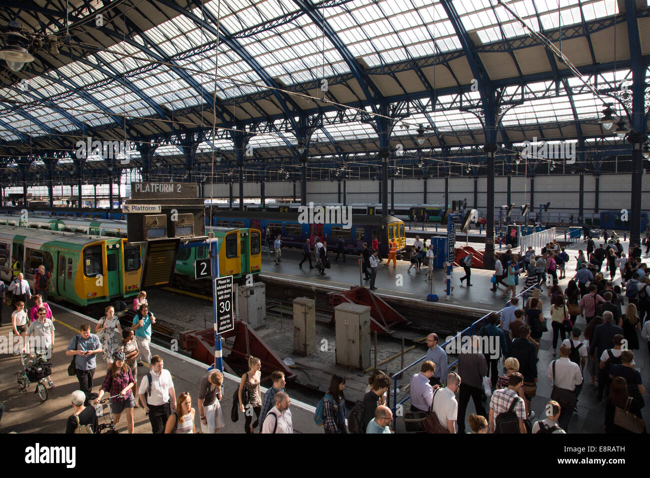 Passengers getting off trains and walking towards ticket gates at Brighton Train Station during a busy summer morning. - Stock Image