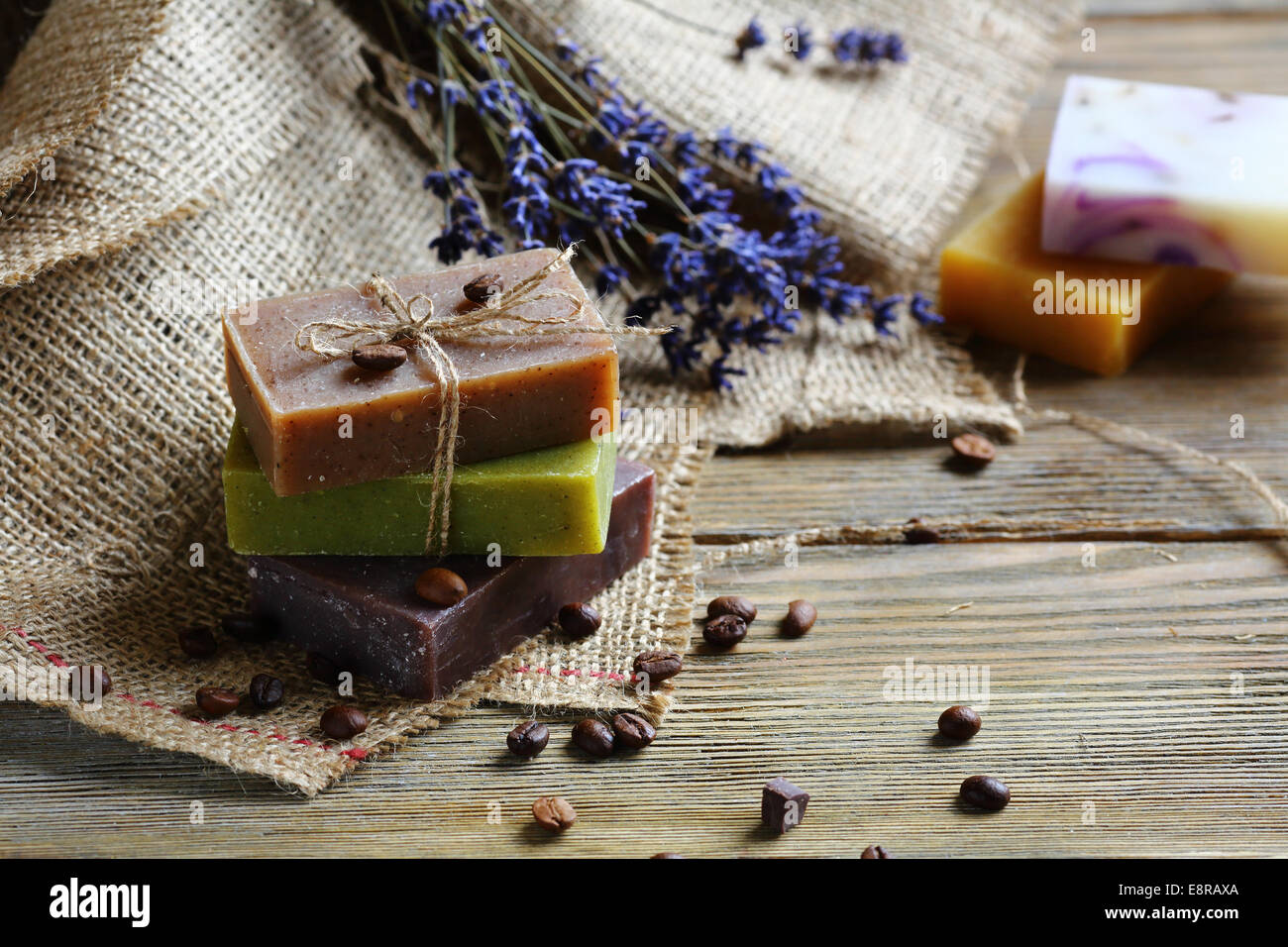 Handmade soap on wooden boards with coffee beans, toiletries close up - Stock Image